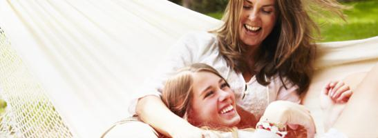 Imagem de duas mulheres deitadas numa rede, a sorrir.