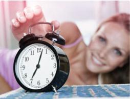 Imagem de um despertador com uma mulher em segundo plano a esticar-se para o desligar.