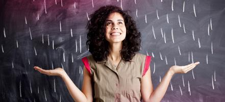 Imagem de uma jovem de pé em frente a um quadro de lousa.