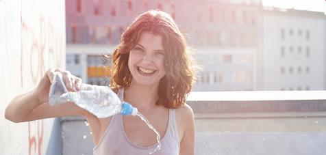 Imagem de uma jovem, a sorrir, a entornar água de uma garrafa que tem na mão.