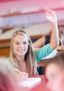 Imagem de uma rapariga jovem numa sala de aula, a sorrir e com a mão no ar para responder a uma pergunta. A imagem ilustra a importância do desenvolvimento sustentável e o modo como a o.b.® promove o ambiente.