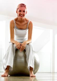 Imagem de uma mulher com roupa de ginástica, sentada numa bola de exercício. Esta imagem ilustra que não há problema em fazer exercício mesmo com o período.