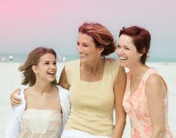 Imagem de três mulheres abraçadas, uma mais jovem à esquerda e duas mais velhas à direita.