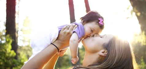 Imagem de uma mulher a pegar num bebé e a beijá-lo.