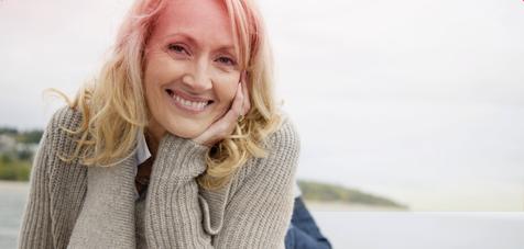 Imagem centrada à esquerda de uma mulher de meia idade, a sorrir.