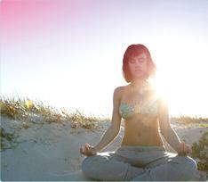 Imagem de uma mulher sentada na praia, a meditar. A imagem ilustra que é possível descontrair e viver normalmente, mesmo quando está com o período.